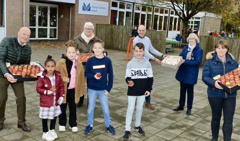 <p>Directeur Arjan Veldsink van de Oranje Nassauschool werd door het bestuur van de buurtvereniging De Polder verrast met een taart en appels .</p>