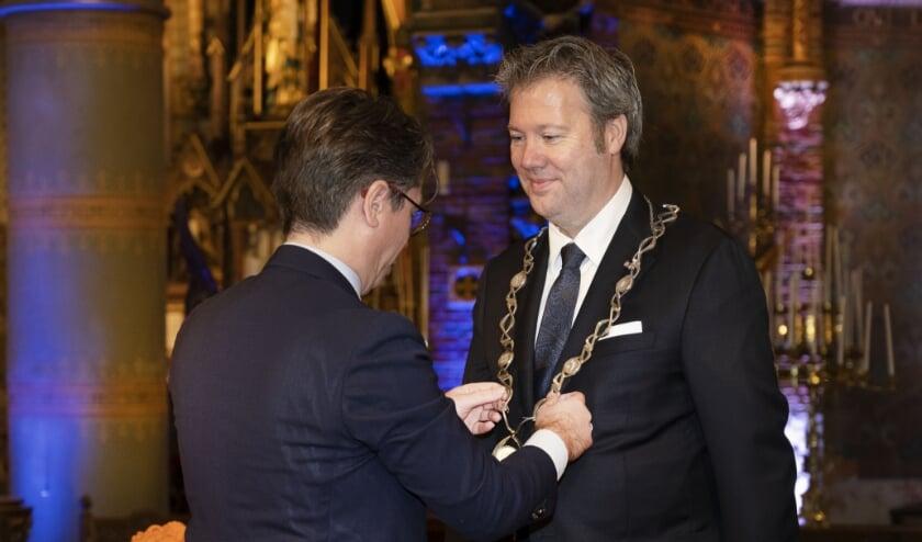 <p>Danny de Vries kreeg maandag in de Sint Fransiscuskerk de ambtsketen omgehangen door zijn echtgenoot Martijn. Foto: Aschwin Snel</p>