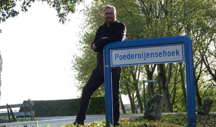<p>Tom van Engelen in het buurtschap Poederoijensehoek, waar hij met jaloerse blik naar kijkt omdat zij wel een buurtschapsbord heeft.</p>