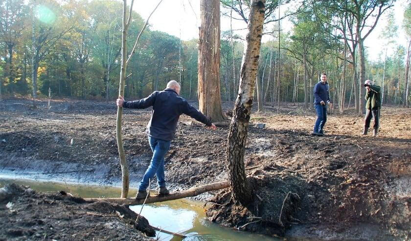 Een gedurfd oversteekje over de nieuwe meander van tuinbaas Vincent Ketelaars. Toon Kemps en Marc Mulders zien het geamuseerd aan.