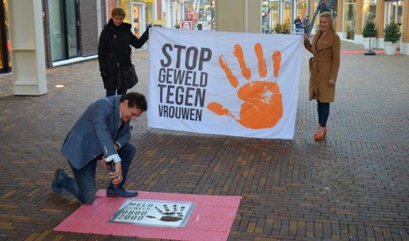 <p>Wethouder Martijn Beek start met het spuiten van het logo op het plaveisel onder de Van Kreelpoort.</p>