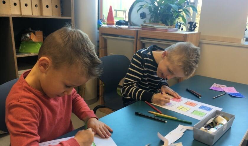 2 leerlingen uit groep zijn geconcentreerd aan hun opdracht aan het werken.