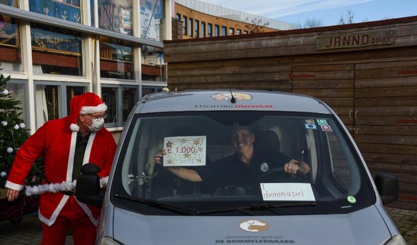 <p>Als Kerstman reikt voorzitter Wim Lambooij in een coronaluwe setting een cheque van 1.000 euro uit aan &eacute;&eacute;n van de gelukkigen.</p>