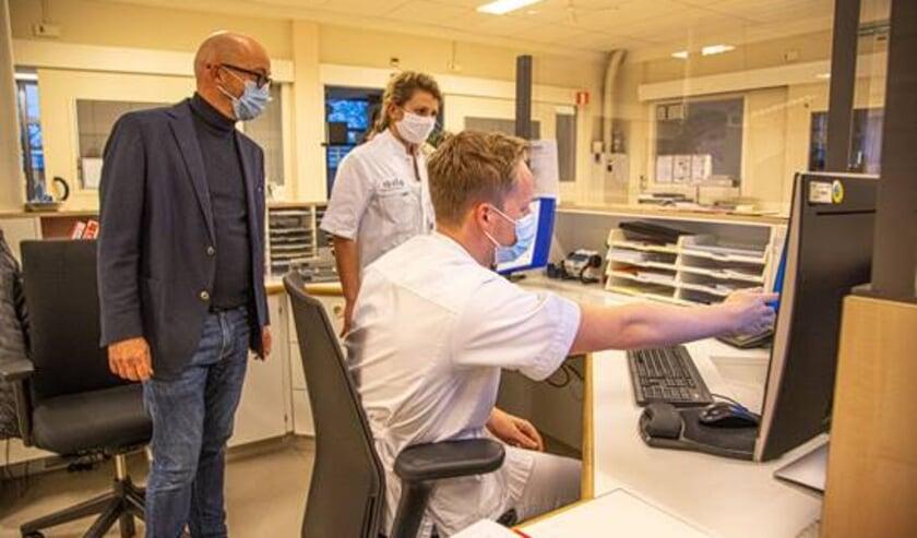 <p>Huisarts Bert van Bremen (links) met Myrna de Man in het monitoringscentrum in Meppel.</p>