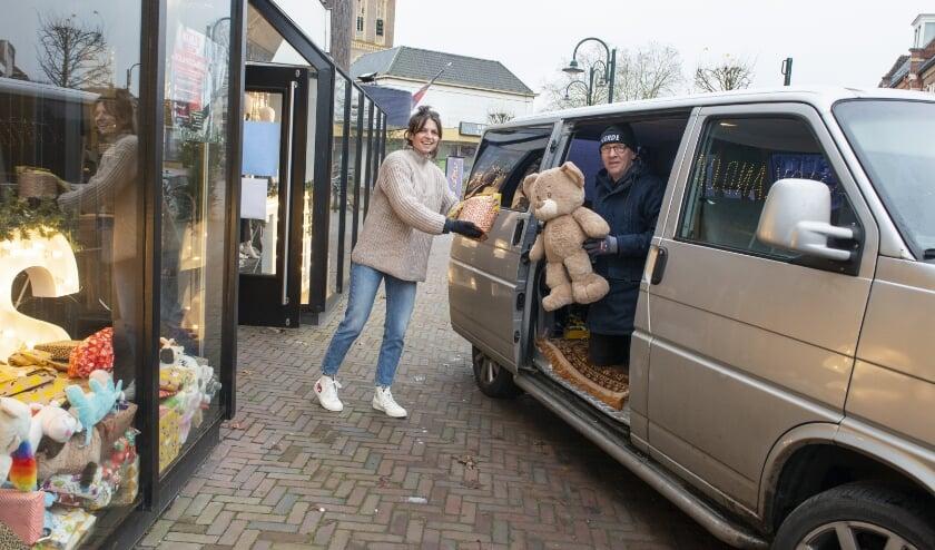 <p>Tiemen Bijsterbosch helpt Nadine Feith van de Heerder kledingwinkel Dick.And.Co met het inladen van de ingezamelde cadeaus voor de Voedselbank. Foto: Dennis Dekker, www.mediamagneet.nl</p>