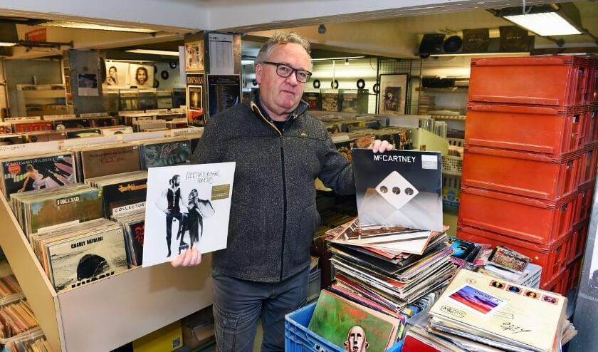Wim Vriezen heeft het album 'Rumours' van Fleetwood Mac in handen, die hij nog wekelijks verkoopt, en de nieuwe LP van Mc Carteney. (foto: Roel Kleinpenning)