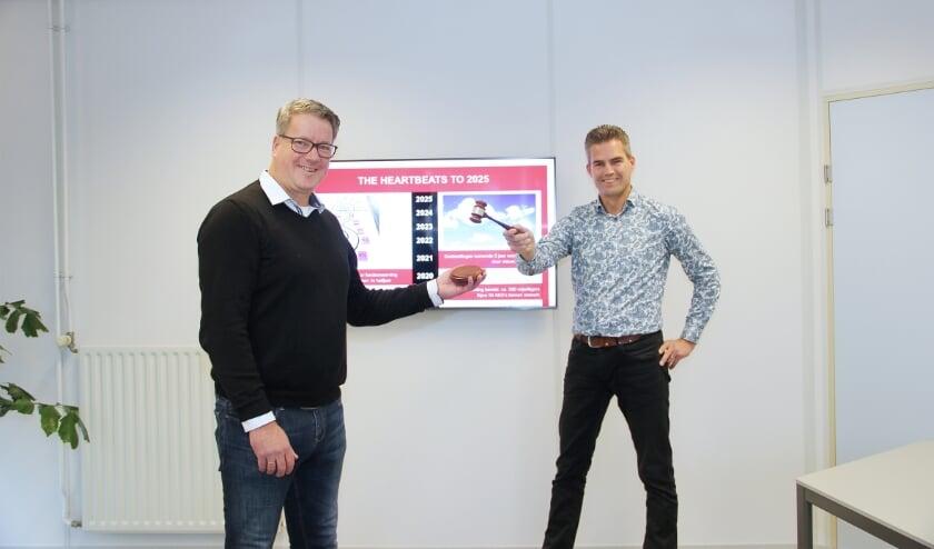 <p>De nieuwe voorzitter van de Stichting AED gemeente Duiven Rob Snijders (links) neemt de voorzittershamer in ontvangst uit handen van de gaande man: Werner Willems.</p>