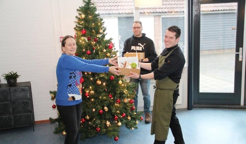 <p>Oscar Grift van Proeflokaal Duiven overhandigt een van de twaalf lunchboxen aan Lucia Dijkstra van Mikado. Op de achtergrond Dominic Beekmans van de welzijnsorganisatie.</p>