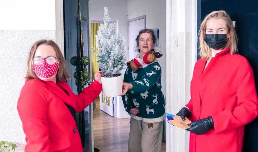 <p>Shanna en Eva overhandigen het boompje aan Alice. </p>