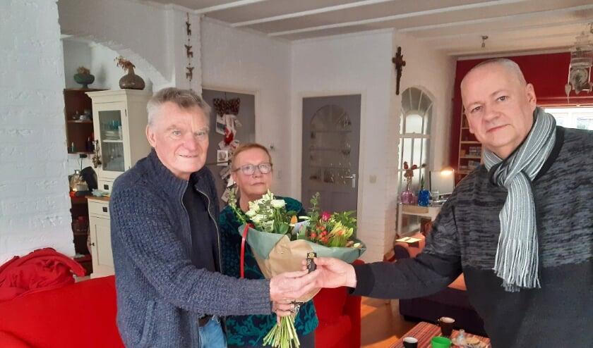 <p>RVW-voorzitter Dick van Deest overhandigt de gouden RVW speld, voor 60 jaar trouw lidmaatschap, en bloemen aan de verraste jubilaris Wim Koenders en zijn vrouw Riet.</p>