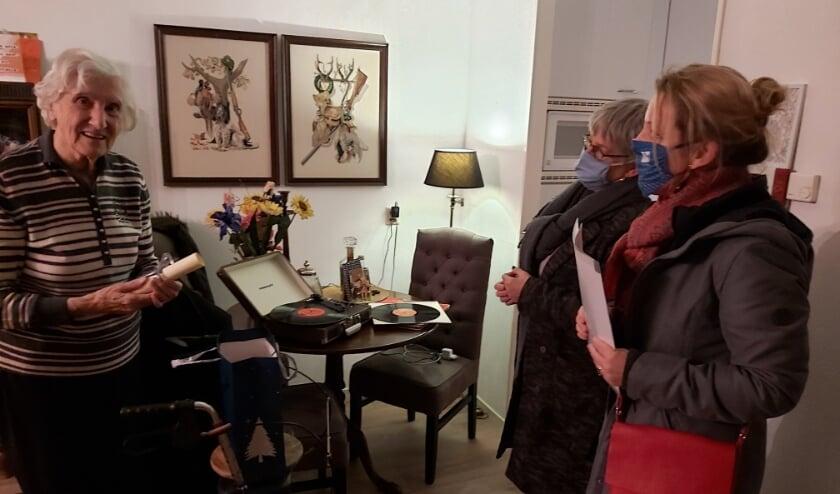 <p>Mevrouw van Lith neem de tas met lekkernijen in ontvangst. Met een klassieke grammofoon zorgt ze zelf voor sfeervolle achtergrondmuziek.</p>