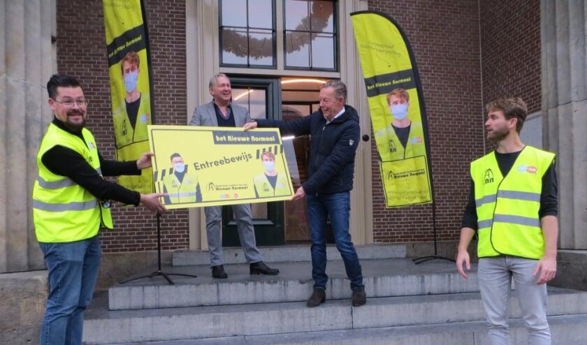 Sjors en Ruud overhandigen het eerste theaterticket voor de show het Nieuwe Normaal aan wethouder Van Noort.