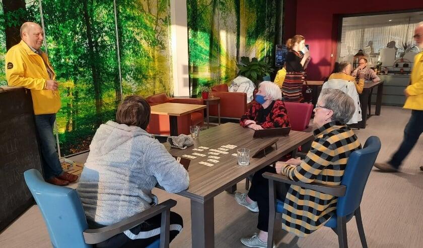 <p>Leden van Gemeentebelang (gele jassen) in gesprek met bezoekers in het WOC.</p>
