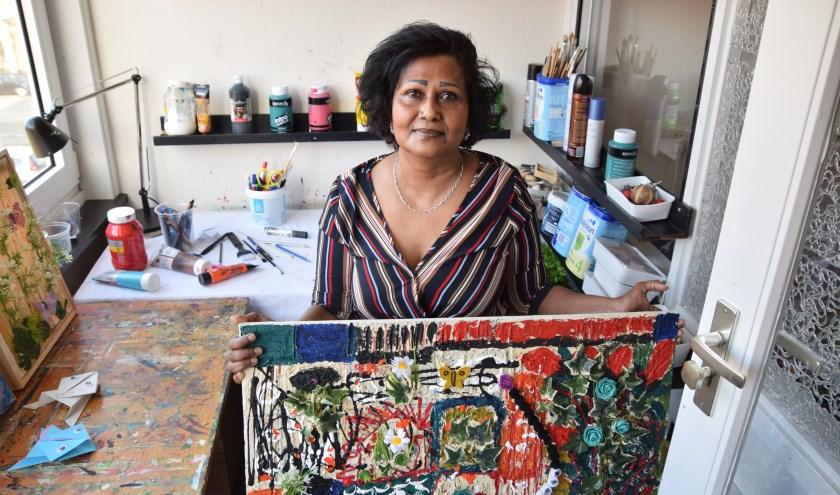Pop Bhageloe in haar werkkamer. Ze maakt en verkoopt schilderijen met een eigen verhaal. (Foto: Timo Oving)