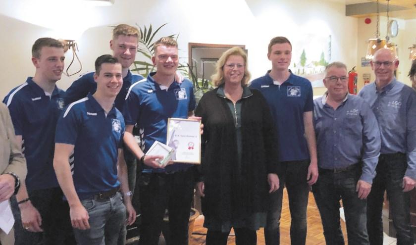 De voetballers van Loo poseren trots met hun prijs samen met prijssponsor Christa Mosterman van Framo.