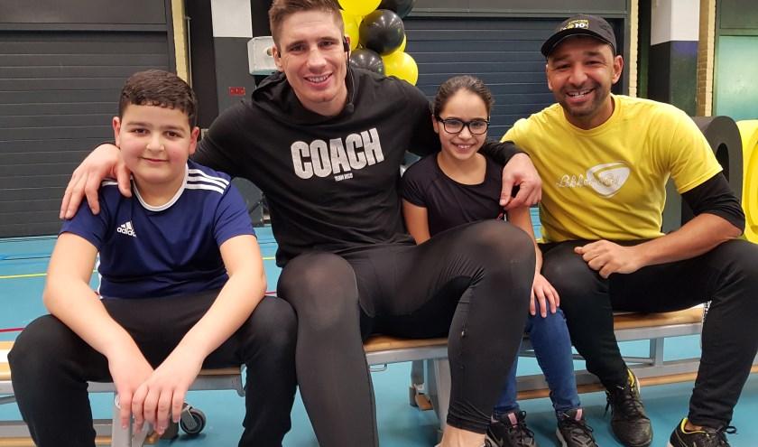 Sayfeddine Haouzi (links) en Amira Zghighad zitten allebei op kickboksen en deden fanatiek mee aan de clinic door Rico Verhoeven. Rechts coördinator schoolsportvereniging Jorge Gomes. (Foto: Emile Hilgers)