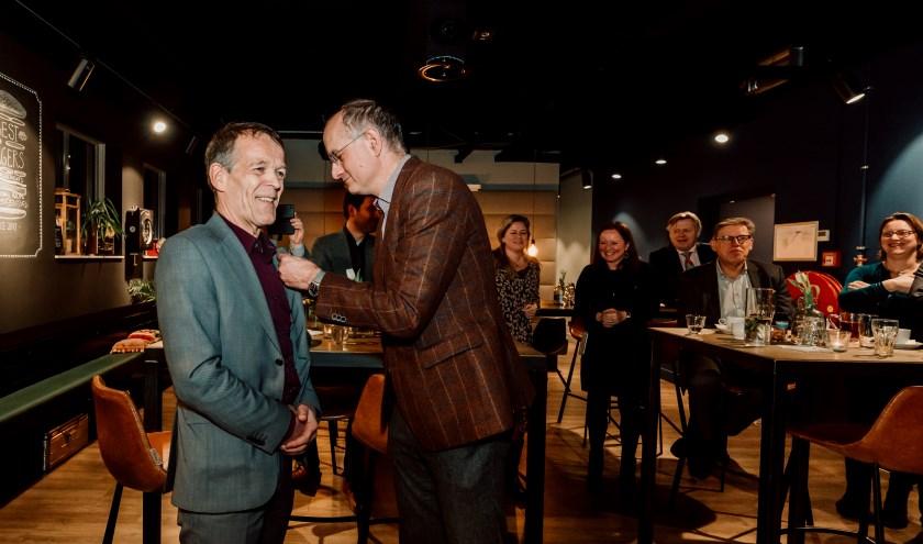Geert Braaksma krijgt de gouden erespeld opgespeld door burgemeester Onno van Veldhuizen.
