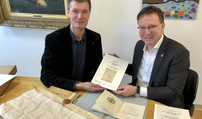 Bij de overhandiging van de inventarisatie door Van Rooijen kreeg de burgemeester een uniek kijkje in oude stukken. (Foto: Lysette Verwegen)