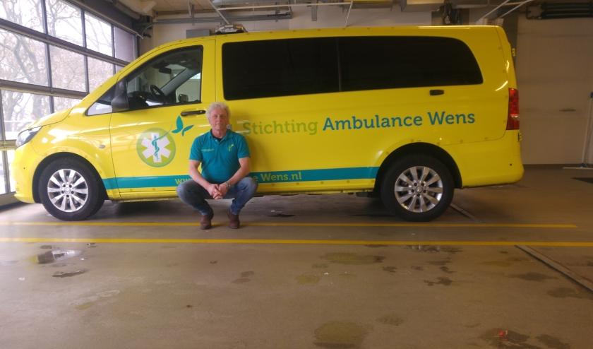 Hein Pannekoek voor één van de auto's van Stichting Ambulance Wens, waarvoor hij vrijwilliger is.