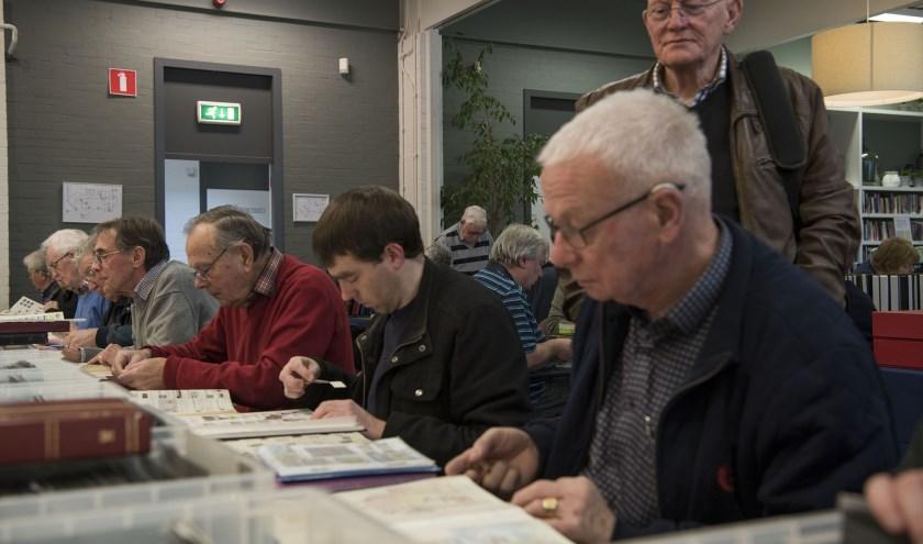 Zoeken naar die postzegel die in de collectie ontbreekt. Het wordt op grote schaal gedaan tijdens de ruilbeurs in Arnhem.
