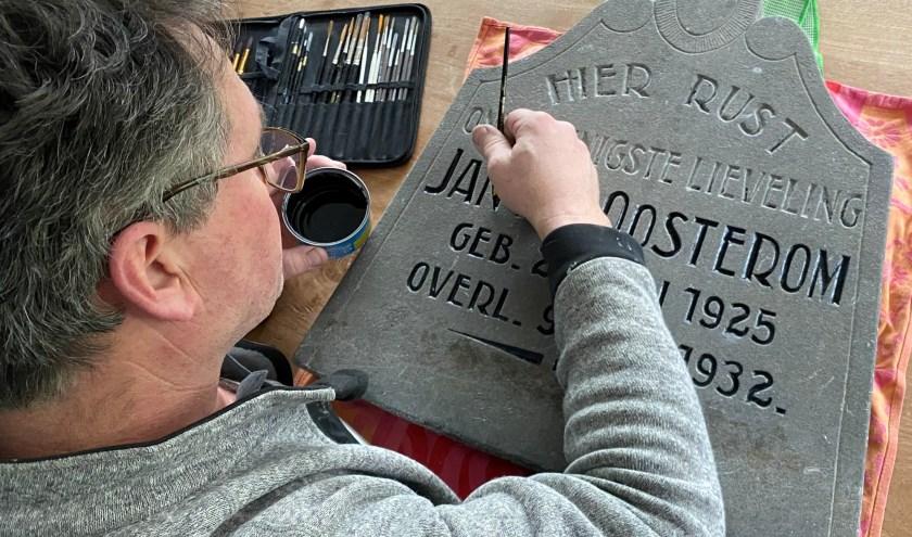 Meester-schilder Henk Bak bezig met het oudste kinderzerkje op de Hervormde begraafplaats. (Foto: Janneke Severs-Hilgeman)