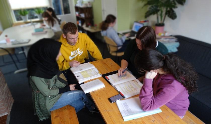 Lennart Bijnagte helpt tijdens groepsgewijze huiswerkbegeleiding. (foto: Martin van Ingen)