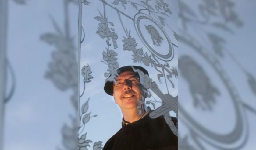 Glaskunstenaar Arend Brons (Neerkant) achter een van zijn glas ontwerpen.