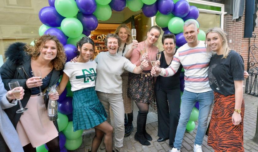 Personeel van Since'04 brengt, samen met eigenaar Joost Middelman (2e van rechts) een toast uit bij de (her)opening van de winkel aan de Hoogstraat. (Foto: Paul van den Dungen)