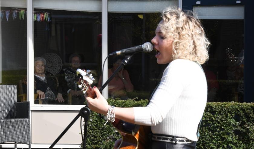 Karlijn Nijkamp zingt voor de ouderen achter glas.