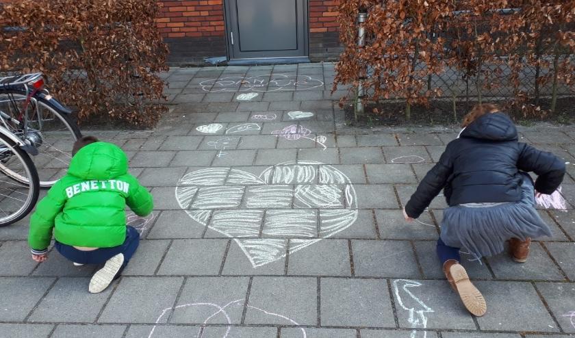 Nick en Lizzy tekenden op de stoep voor het Medisch Centrum in Oudewater hartjes en bedankjes voor het medisch personeel. (Aangeleverde foto)
