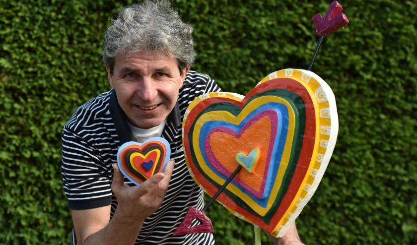 Kunstenaar Maarten van der Geest, de ontwerper van de Poort van Duiven, met zijn creatie van een meerkleurig hartje als symbool voor inclusieve samenwerking.