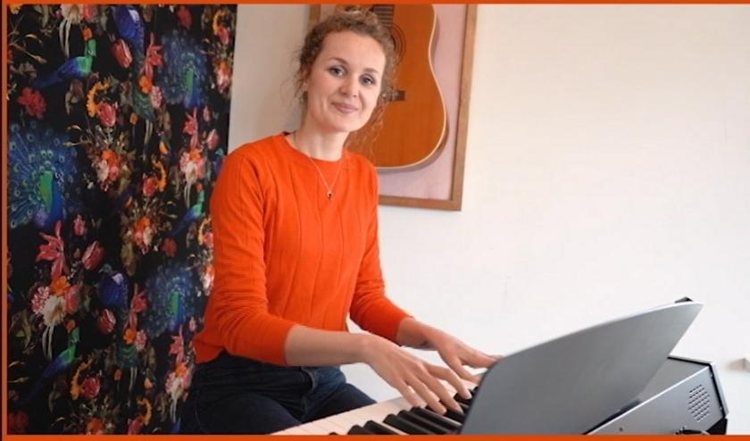 Een screenshot van het eerste filmpje van Thuisbezorgd: musicaldocent Eva-Marijn de Vries heeft een meezingliedje opgenomen.