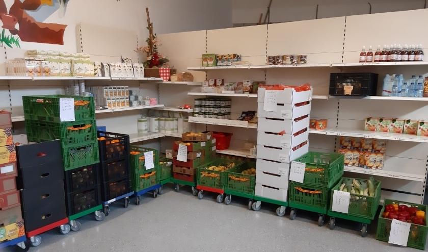 In de voedselbankwinkel vullen gastvrouwen tijdens de uitgifte een tas met verse producten voor de afnemer. Afnemers komen nu niet in de winkel. (Foto: Voedselbank)