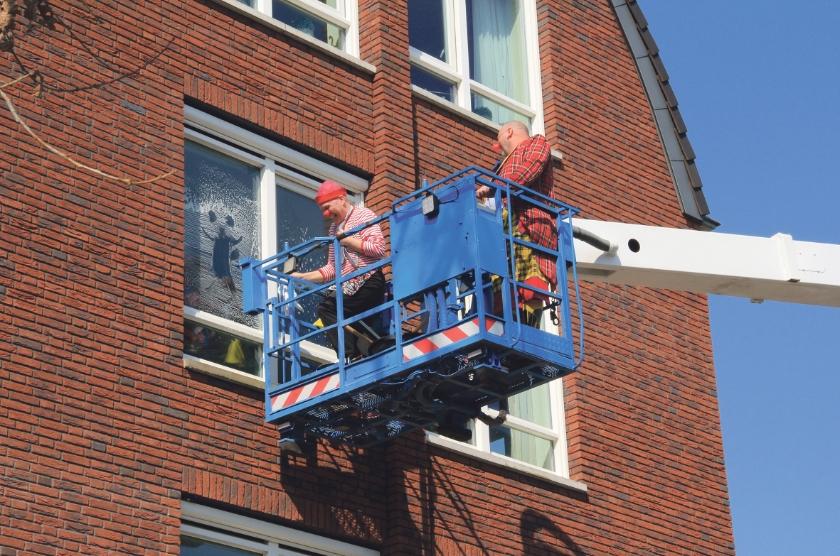 'Cleaning clowns' wassen de ramen bij Thuvine en maken ondertussen contact met de bewoners.
