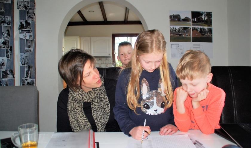 Een nieuwe situatie, die toch al begint te wennen: Susan Quirijnen en haar drie kinderen Lars, Lotte en Jelle samen aan het werk aan één tafel.