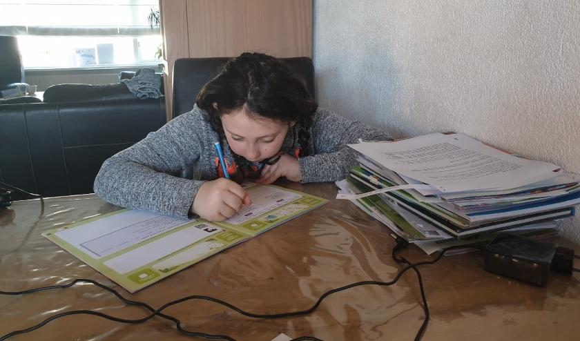 Demi Kellenaers is thuis ijverig bezig met haar huiswerk.