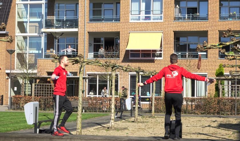 Buurtsportcoaches Nick Linnenbank en Bram van Geffen van Welzijn Bommelerwaard trainen, op gepaste afstand, samen met de bewoners van De Leyenstein. Vanaf deze week worden er op meer plekken beweegsessies gehouden.