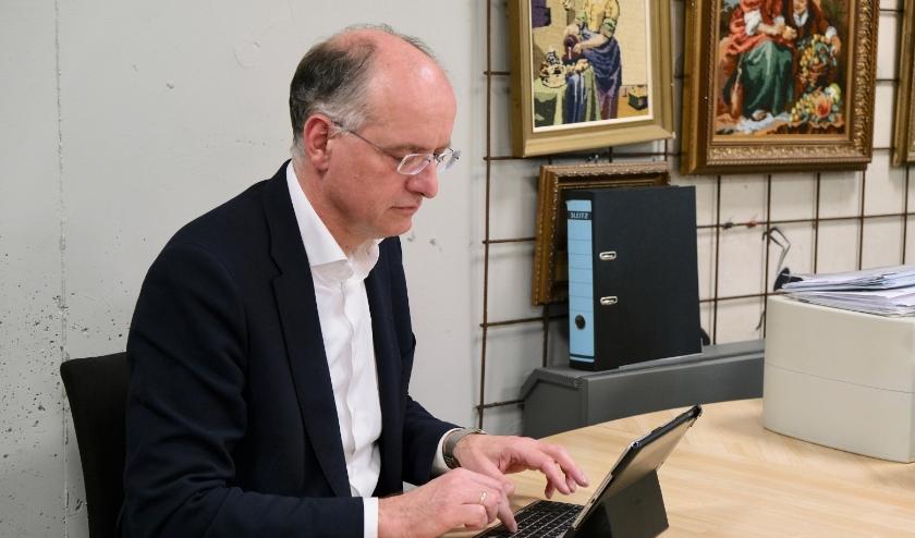 Burgemeester Onno van Veldhuizen beantwoordt tussen de bedrijven door, op de redactie van1Twente Enschede, zijn mail. (Foto: PR)
