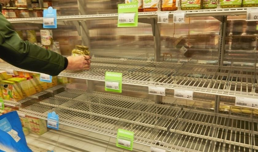 Lege schappen in supermarkt doordat Nederlanders in winkels massaal levensmiddelen hamsteren uit angst voor de uitbraak van corona.