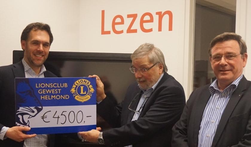 President John Raaijmakers (l) overhandigt cheque aan Willy van der Linden, rechts Lambert van der Meulen.