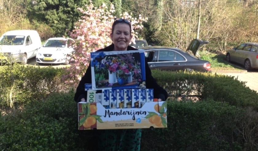 Joke Klein, vrijwilliger van de Voedselbank Rhenen, met een doos vol legpuzzels. (Foto: Louise Barf)