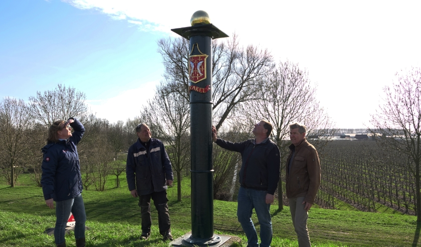 Restaurateur Femke Rinkel en smid Wim van de Helm (links van de paal) bekijken samen met Gerard van Doorn, gemeente Zaltbommel, en Gerrit Ermstrang (rechts), dorpsraad Brakel, de gerestaureerde grenspaal.