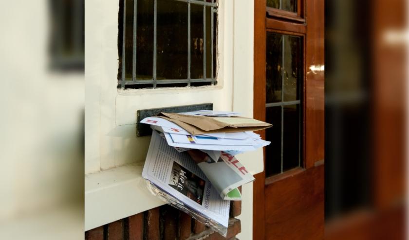 Deur met volle brievenbus.