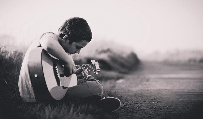 Jongen speelt gitaar.