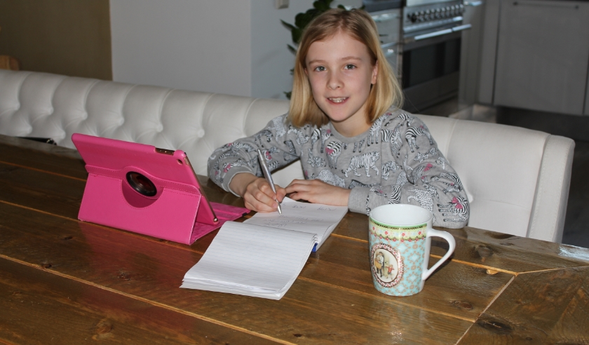 Gewapend met roze iPad, schrijfblok en beker thee, slaat Isabella (9) zich dapper door het thuiswerken heen.