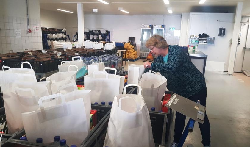 Greet Blom inspecteert de voedselpakketten bij de Voedselbank Nederveluwe. (foto: Kees Stap)