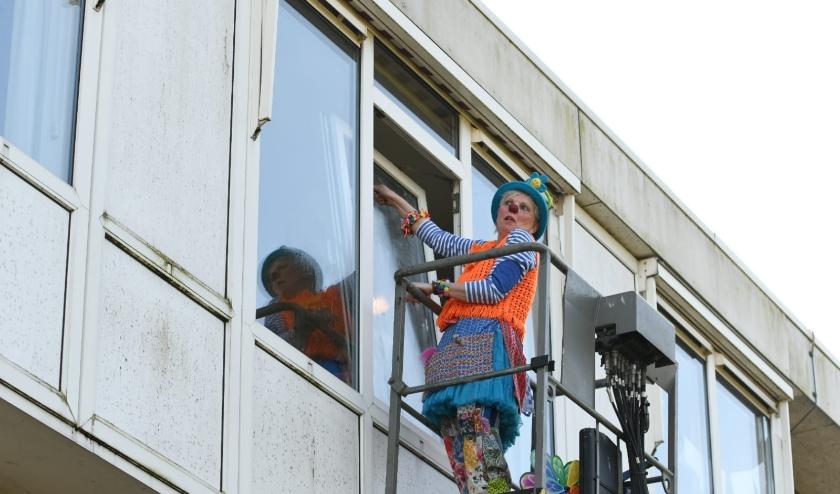 Toet zeemt de ramen om haar stralende glimlach goed zichtbaar te maken voor de ouderen aan de andere kant.