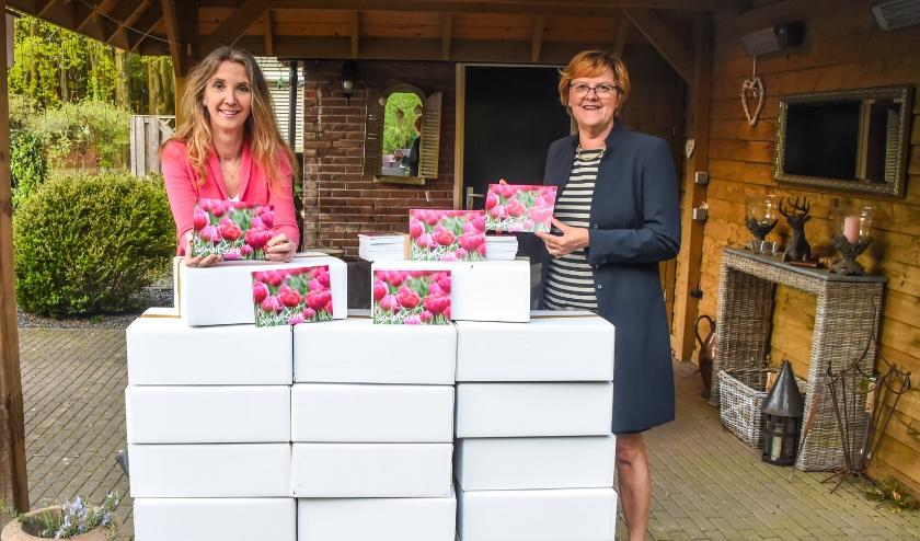 Nel Verkroost (rechts) neemt een doos kaarten in ontvangst van natuurfotograaf Yvette van den Berg voor verspreiding in De Bilt en Bilthoven.