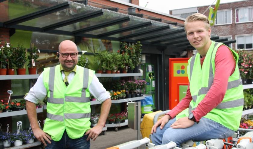 Gerbert en Wessel bij de schoongemaakte winkelwagentjes bij de ingang van de supermarkt