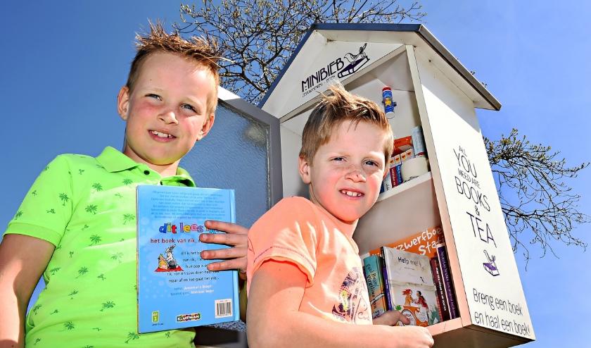 Dirk (links) en Rien Smits vullen de Minibieb in Etten bij. (foto: Roel Kleinpenning)